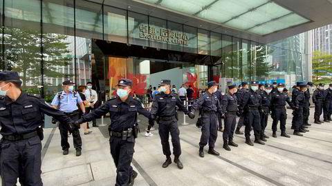 Politi oig sikkerhetsvakter omringet hovedkontoret til eiendomsselskapet China Evergrande for å beskytte det mot rasende folkemengder på mandag. Aksjekursen er i fritt fall og risikoen for en konkurs øker.