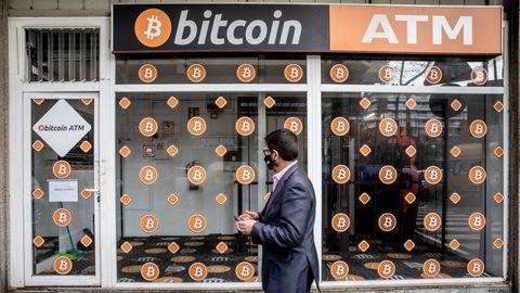 Prisen på bitcoin faller fredag. Her passerer en fotgjenger en bitcoin-minibankkiosk i Barcelona i Spania.