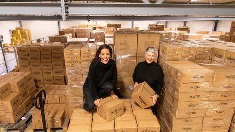 Kristin Vassnes (til venstre) og Linda Olsrud i Sögne Home blant noen av de 56.000 koppene som akkurat har ankommet lageret fra Kina.