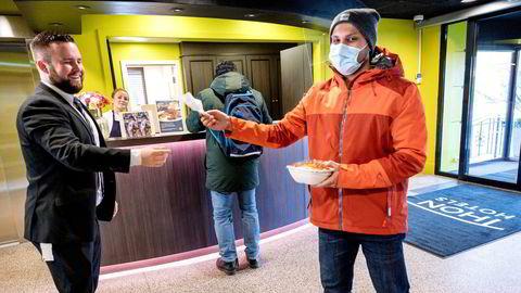 Hotellsjef Daniel Breivik i Thon Hotel Slottsparken (til venstre) gir bestikk til kunde Rohit Joshi som har sikret seg en forundringsporsjon med overskuddsmat fra frokostbuffeten.