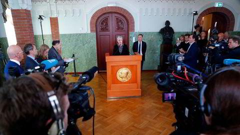 Berit Reiss-Andersen, leder av Nobelkomiteen, og komiteens sekretær Olav Njølstad (i bakgrunnen), offentliggjør her vinneren av fredsprisen på Nobelinstituttet i Oslo.