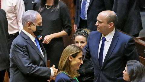 Israels avtroppende statsminister Benjamin Netanyahu tar den påtroppende statsministeren Naftali Bennett i hånden etter at voteringen i nasjonalforsamlingen Knesset søndag gjorde det klart at det blir regjeringsskifte.