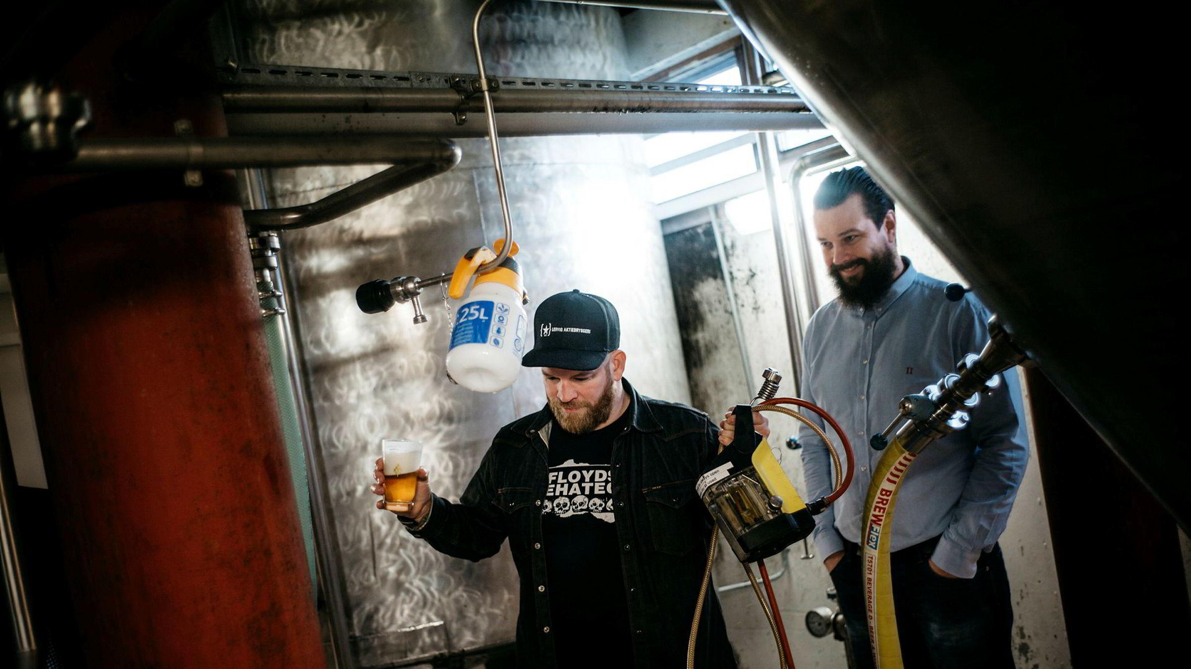Daglig leder i Lervig Aktiebryggeri Anders Kleinstrup, til høyre, og bryggerimester Mike Murphy inspiserer en prøve fra en av tankene. Foto: Tommy Ellingsen