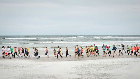 En remse løpere kjemper seg gjennom motvinden på stranden Dueodde. Dette er Etape Bornholms kanskje mest sagnomsuste løp, der hvert fraspark blir gjort i en sand som er så finkornet at den visstnok brukes i timeglass.