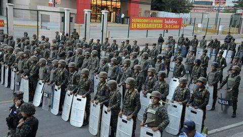 Soldater står klare til å stoppe en protestmarsj etter at president Juan Orlando Hernández søndag ble gjenvalgt.