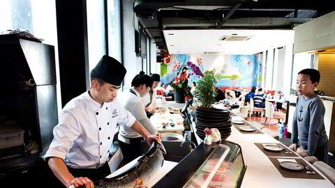 Illustrasjonsfoto: Den erfarne kokken Feng Jiang på restauranten Haiku gjør en skotsk laks klar for servering. Kinesiske forbrukere er nå redde for koronasmitte fra både norsk og skotsk laks.