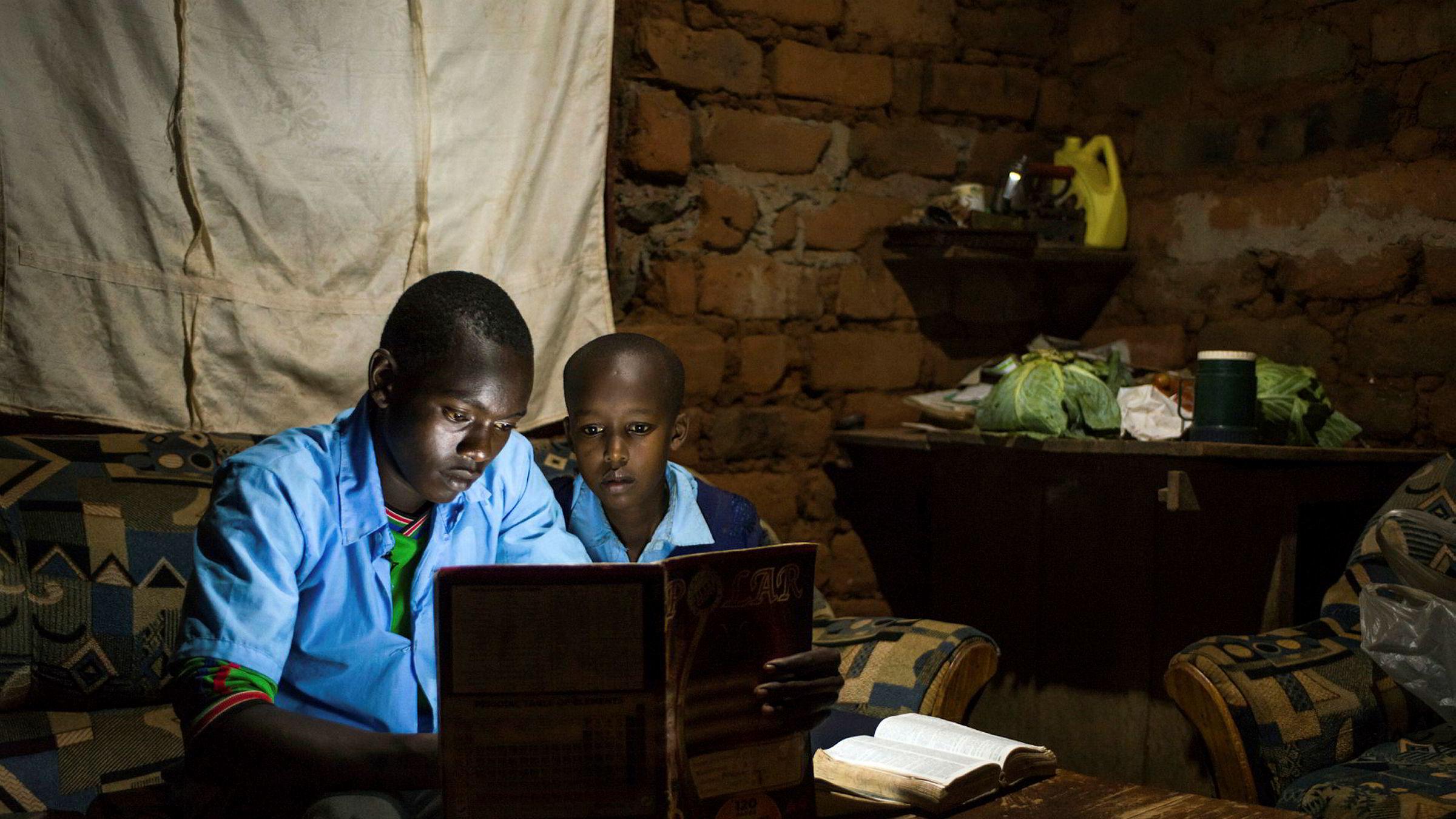 Statistikk viser at vestlig næringsliv for tiden trekker seg tilbake fra de fattigste landene. Vestlige banker er på vei ut av Afrika sør for Sahara, og direkte utenlandsinvesteringer i enkeltbedrifter (FDI) går ned, særlig i de fattigste landene, skriver innleggsforfatteren. Her leser to elever i Ndela Village i Kenya ved hjelp av en lyspære drevet med solenergi fra M-Kopa, som Norfund samarbeider med.