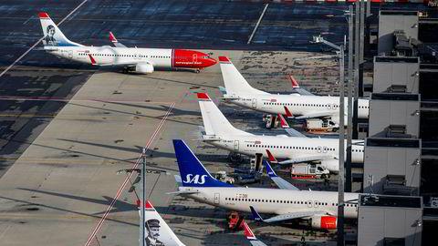 Norwegian og SAS fly står parkert på Oslo lufthavn.