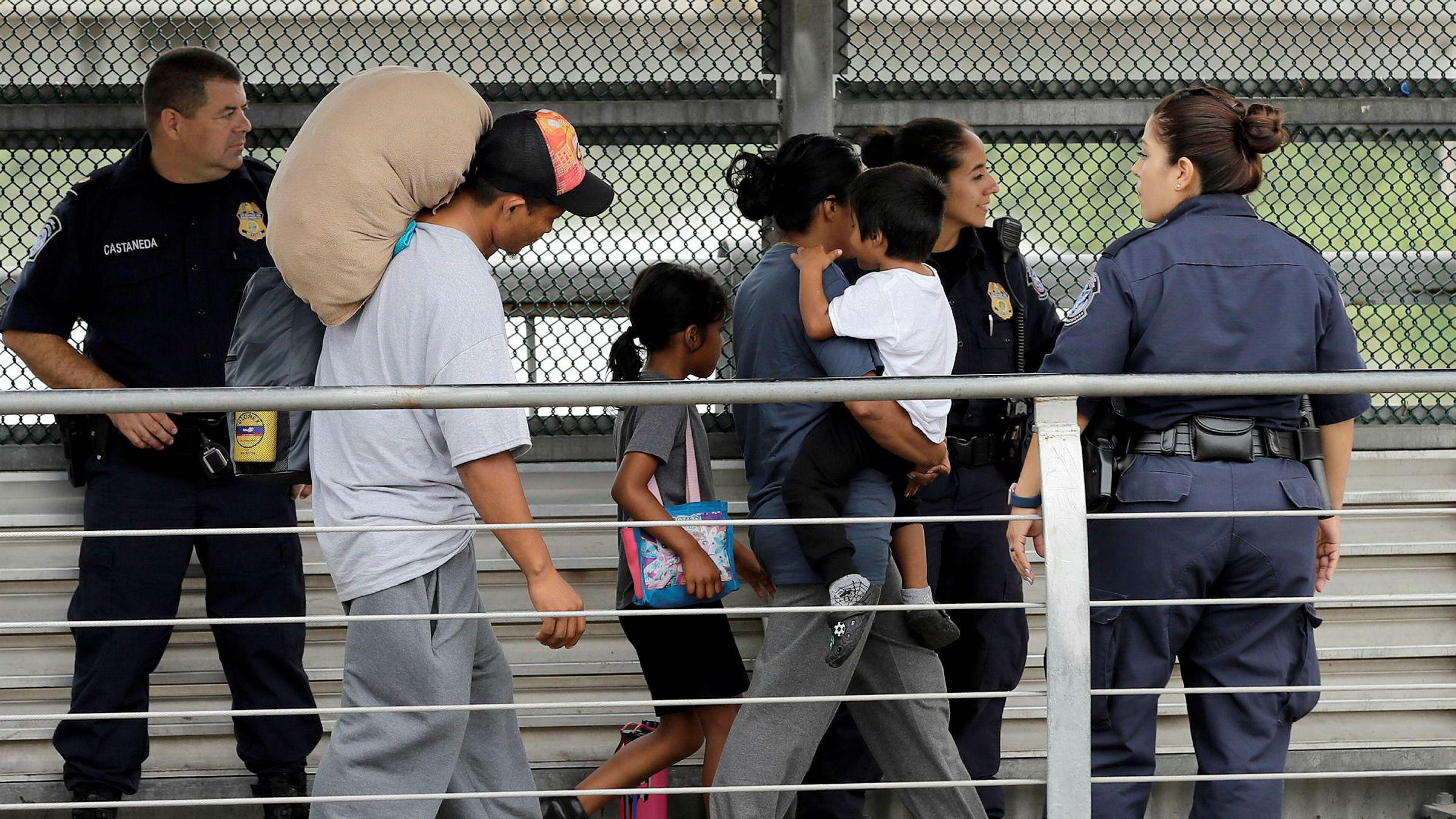 En honduransk familie eskorteres tilbake over grensa mot Mexico av amerikansk grensepoliti. Familien sa de fikk beskjed om at de ville bli skilt fra barna og valgte å frivillig dra tilbake til Mexico.