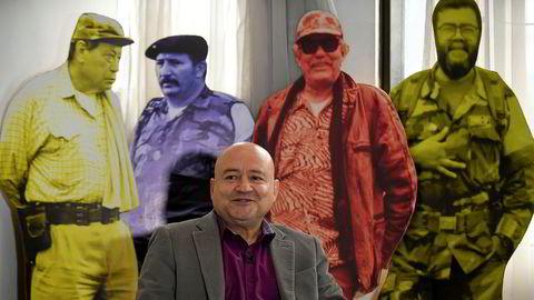 FARC-toppen Carlos Lozada i et intervju med AFP i Bogata 9. august. I bakgrunnen står de tidligere FARC-lederneManuel Marulanda Velez, Jorge Briceno Suarez, Jacobo Arenas og Alfonso Cano. Nå blir FARC et politisk parti.