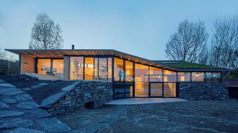 Bølgende. Huset på Finnøy har grønt sedumtak og er bygget inn i det skrånende terrenget.