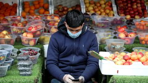 Myndigheter over hele verden deltar i det teknologiske kappløpet om å få kontroll over koronaviruset gjennom innsamling og analyse av befolkningens personlige data. Bildet viser en mann med munnbind ser på mobiltelefonen mens han venter på kunder i Birmingham 30. mars i år.