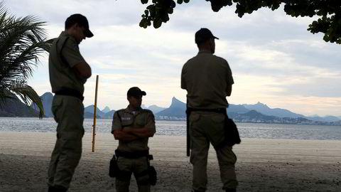 Lokalt politiet patruljerer stranden Icarai ved Sukkertoppen i Brasil torsdag. Landet innfører enda strengere regler nå. Foto: Silvia Izquierdo