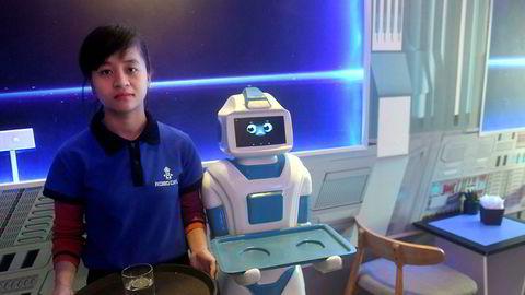 To av servitørene ved Hanois nyåpnede Robo Cafe. Til høyre er roboten «Mortar» klar til å servere kundene drikkevarer og snacks, og beveger seg over gulvet ved hjelp av elektromagnetiske sensorer.