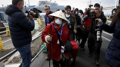 En passasjer er omgitt av media i det hun kommer i land fra det virusrammede cruiseskipet Diamond Princess som ligger til kai i Yokohama i Japan.