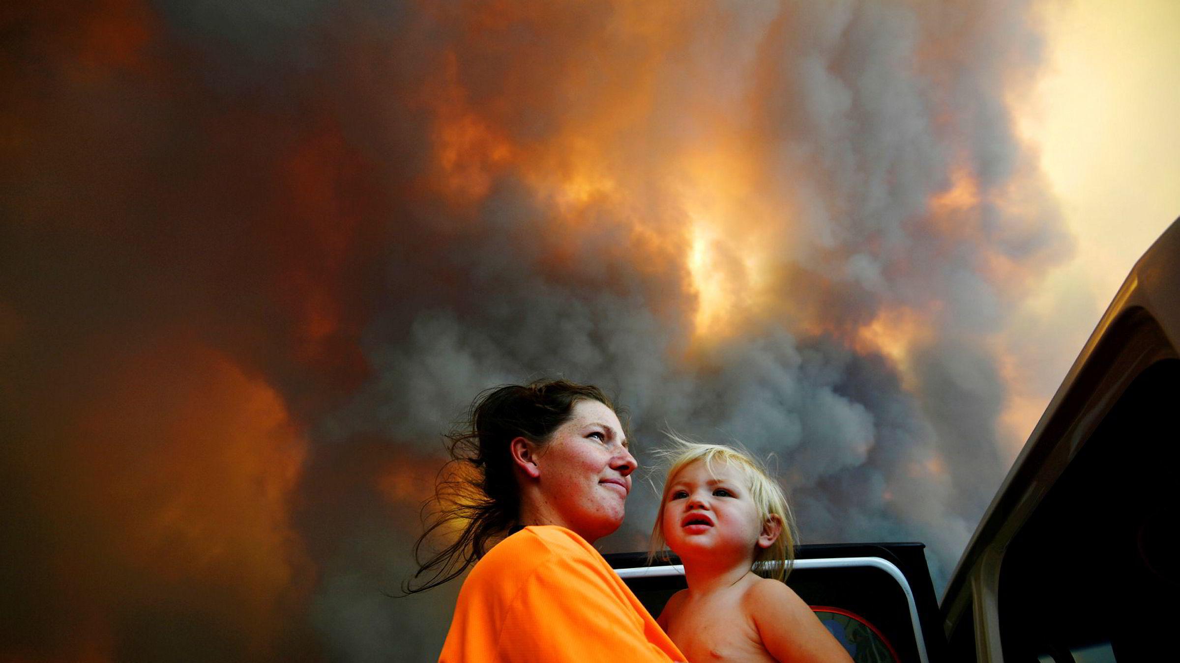 Ekstremvær truer veksten i verdensøkonomien, ifølge IMF. Det vises til orkaner i Karibia, flommer i østlige Afrika, tørke i sørlige Afrika – og tørke og branner i Australia. Bildet viser Sharnie Moren og hennes 18 måneder gamle datter Charlotte som ser på tykk røyk fra buskbranner nær Coffs Harbour i Australia i november.