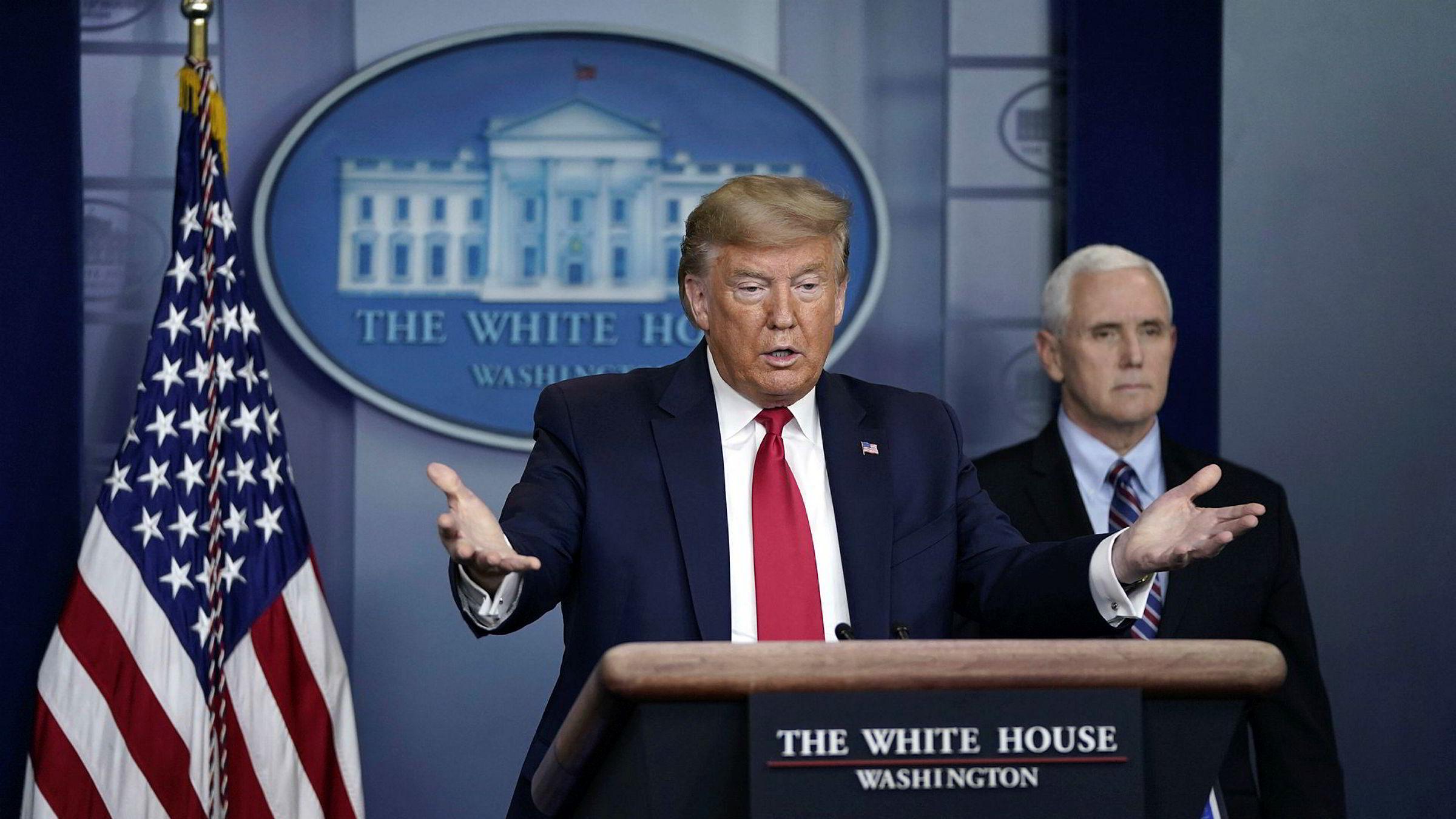 President Donald Trump og visepresident Mike Pence i bakgrunnen. Fredag ble krisepakken på 2000 mrd. dollar vedtatt av Representantenes hus.