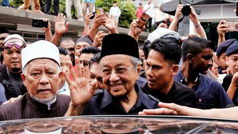 Statsminister Mahathir Mohamad (i midten) vinket til folkemengden på vei ut av nasjonalmoskeeen i Kuala Lumpur etter fredagsbønnen.