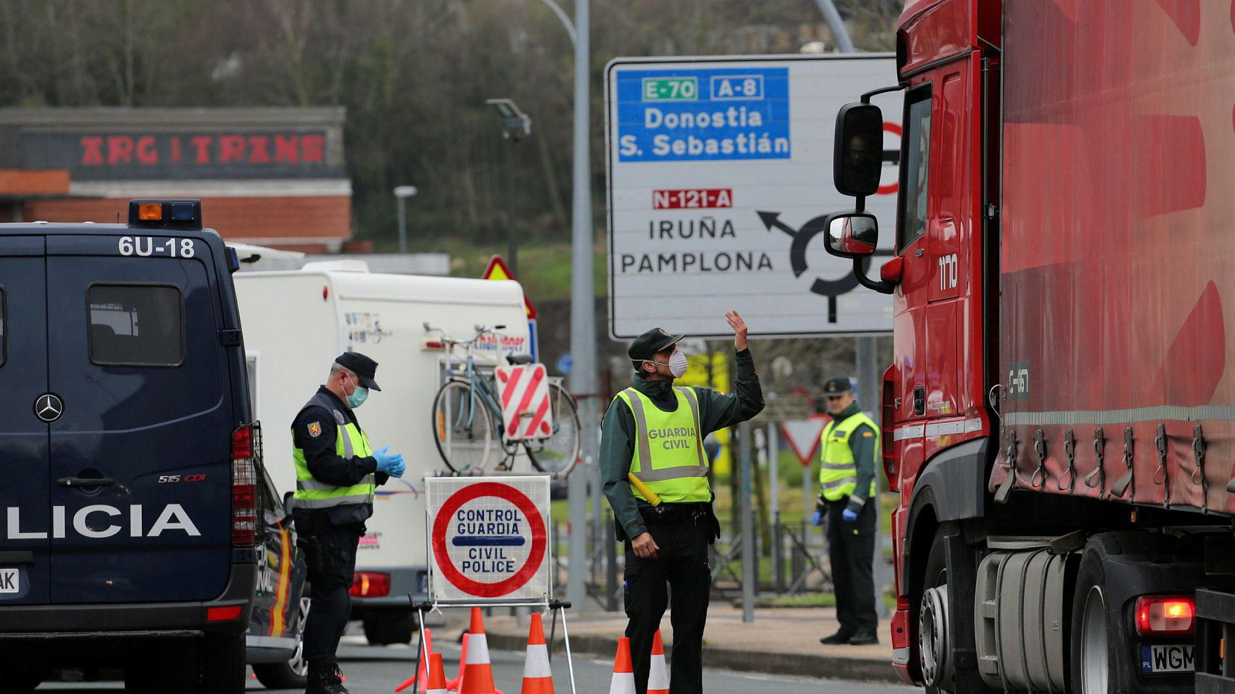 Maskerte spanske Guardia Civil og politi sjekker lastebiler som vil inn i Spania fra Frankrike. Strenge restriksjoner på grensepasseringer er innført over hele Europa.
