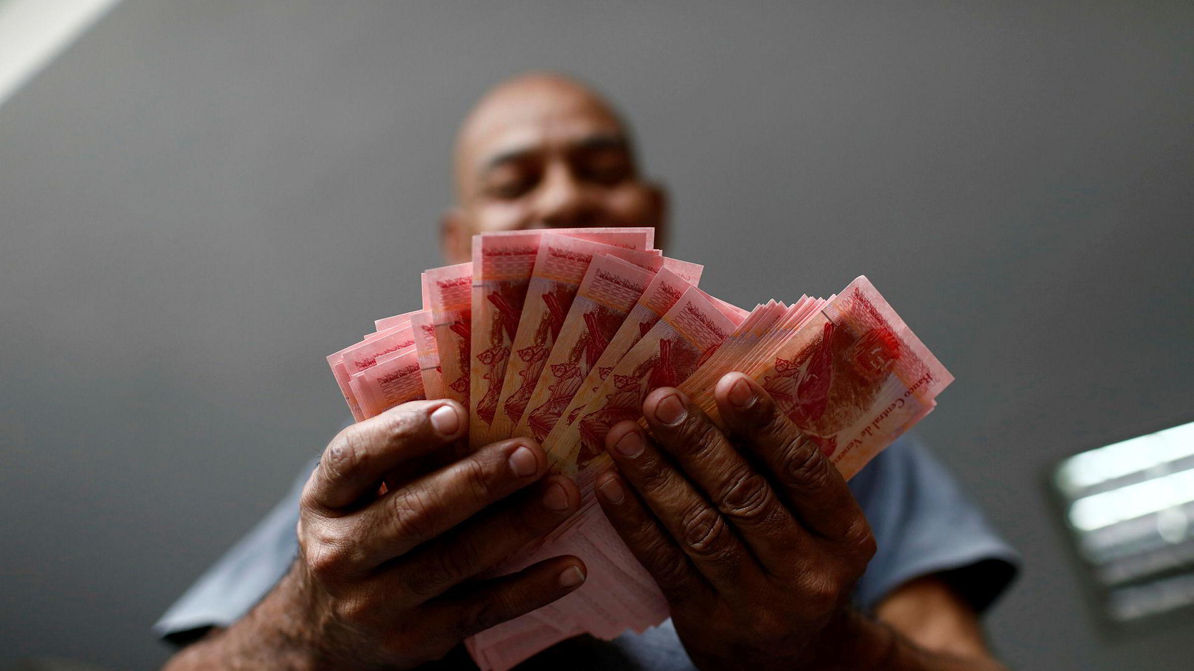 Venezuela sliter med enorm inflasjon. Nå fjernes flere nuller på pengesedlene. På bildet teller en tjenestemann penger på en parkeringsplass i Caracas i mai.