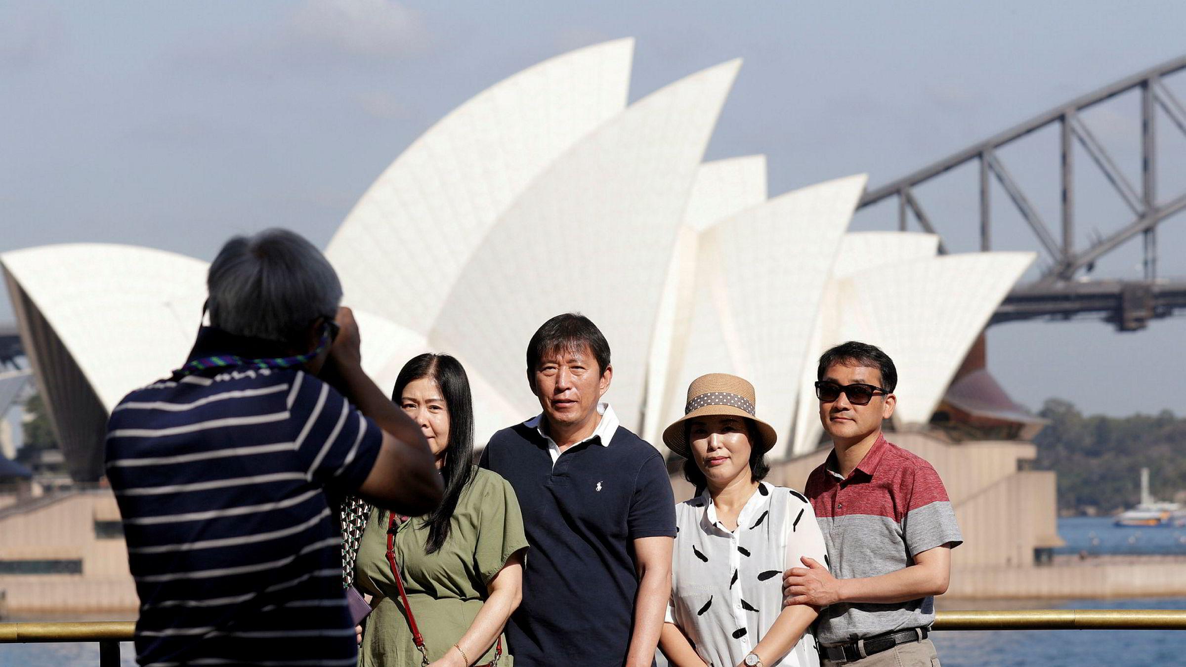 Regjeringen i Australia innfører innreiseforbud for reisende fra Kina. Bildet viser turister foran Operahuset i Sydney.
