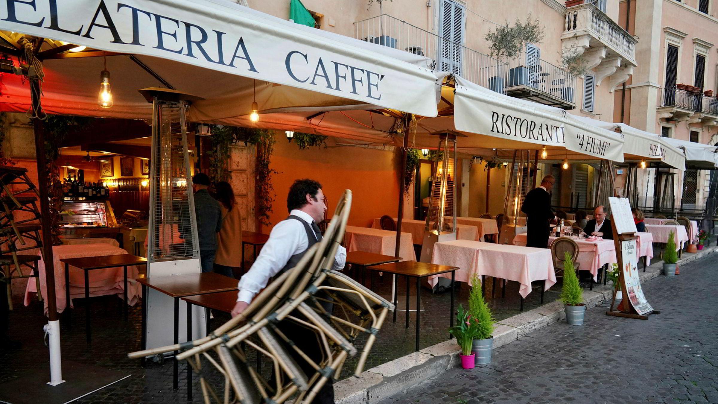 Kelnere tar inn stoler og bord når en restaurant i Roma må stenge klokken 18 på grunn av koronaviruset.