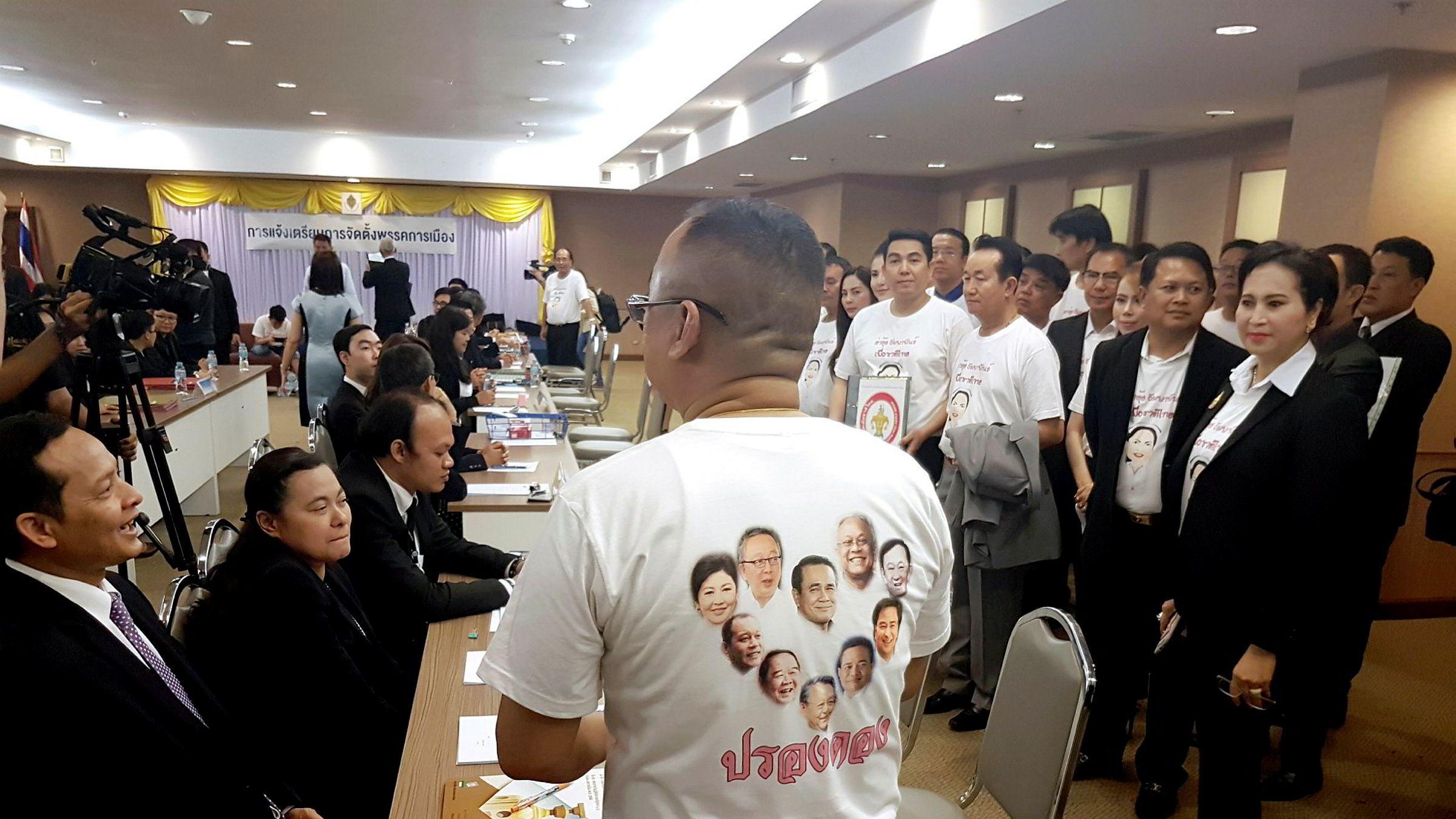 Et medlem av Phuar Chart Thai partiet, med t-skjorte med bilder av Thailands tidligere og nåværende statsministere, venter på å registrere sitt parti, etter at det ble tillatt i Thailand den siste uken – nesten fire år etter at militæret tok makten. Nå kan det gå mot demokratiske valg i løpet av det neste året. Det kan bli kaotisk med nye politiske allianser.