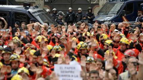 Brannmenn løfter nevene i protest mot politiets fremferd i forbindelse med søndagens folkeavstemning. Store deler av Barcelona ble lammet under tirsdagens generalstreik.