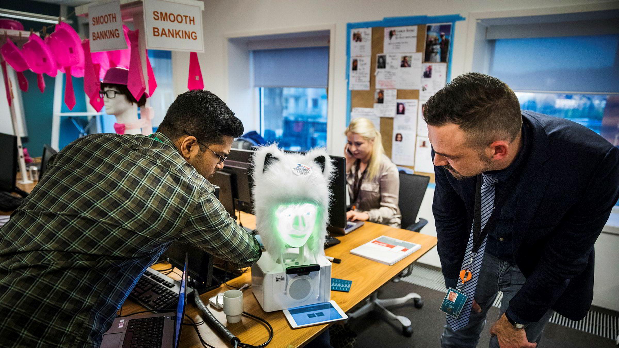 Jerin Kurian (fra venstre), Trine Lysen og Jan Thomas Lerstein jobber med å utvikle digitale kundeservice-løsninger. Roboten «Furhat» bruker menneskelig mimikk mens den prater.