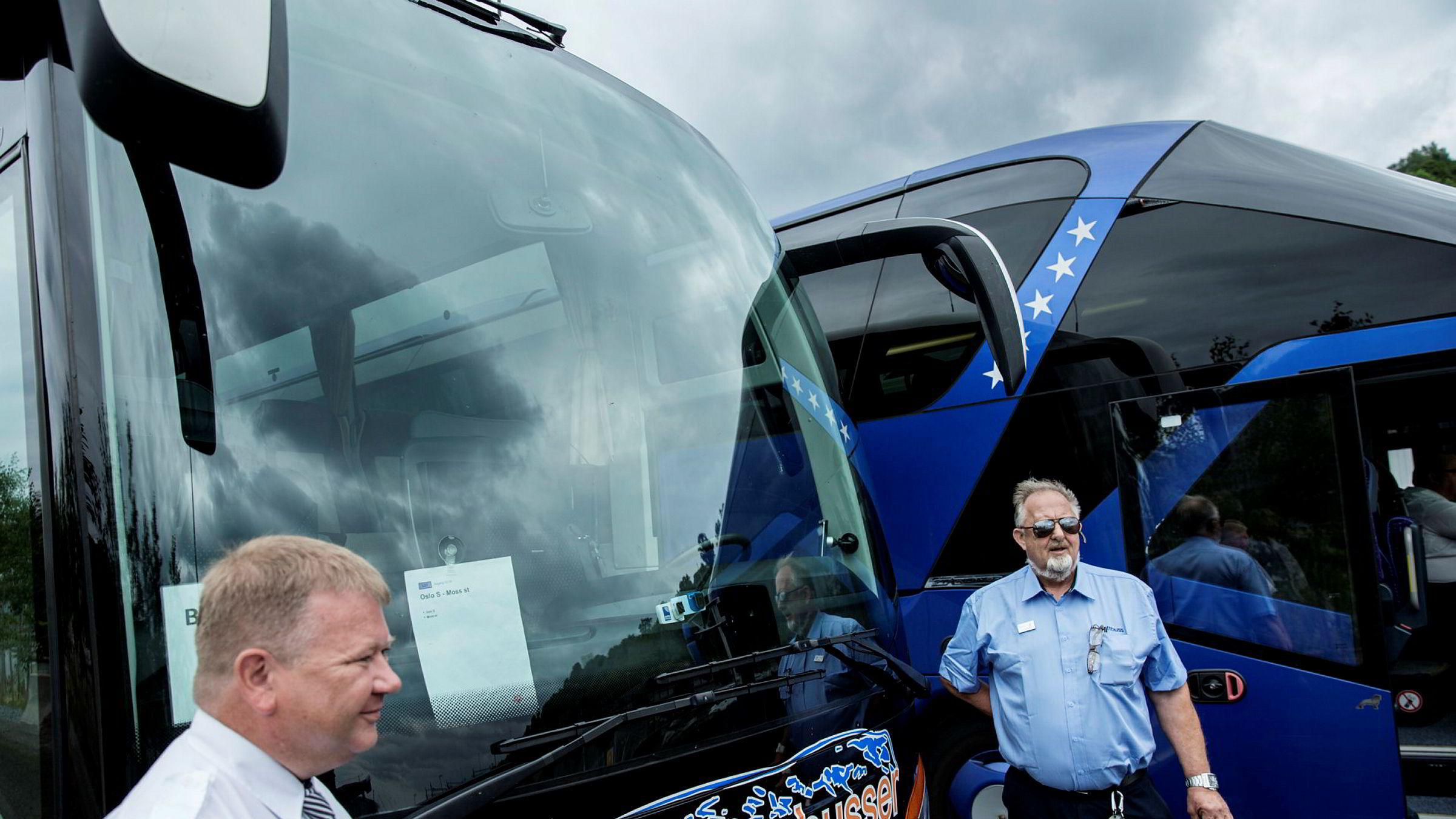 Oskar Andreas Skulstad (til venstre) og Even Haugen kjører buss for tog i sommer. En rekke busser som skal frakte NSBs passasjerer i sommer står parkert nær Sørenga i Oslo mellom rushtidene.