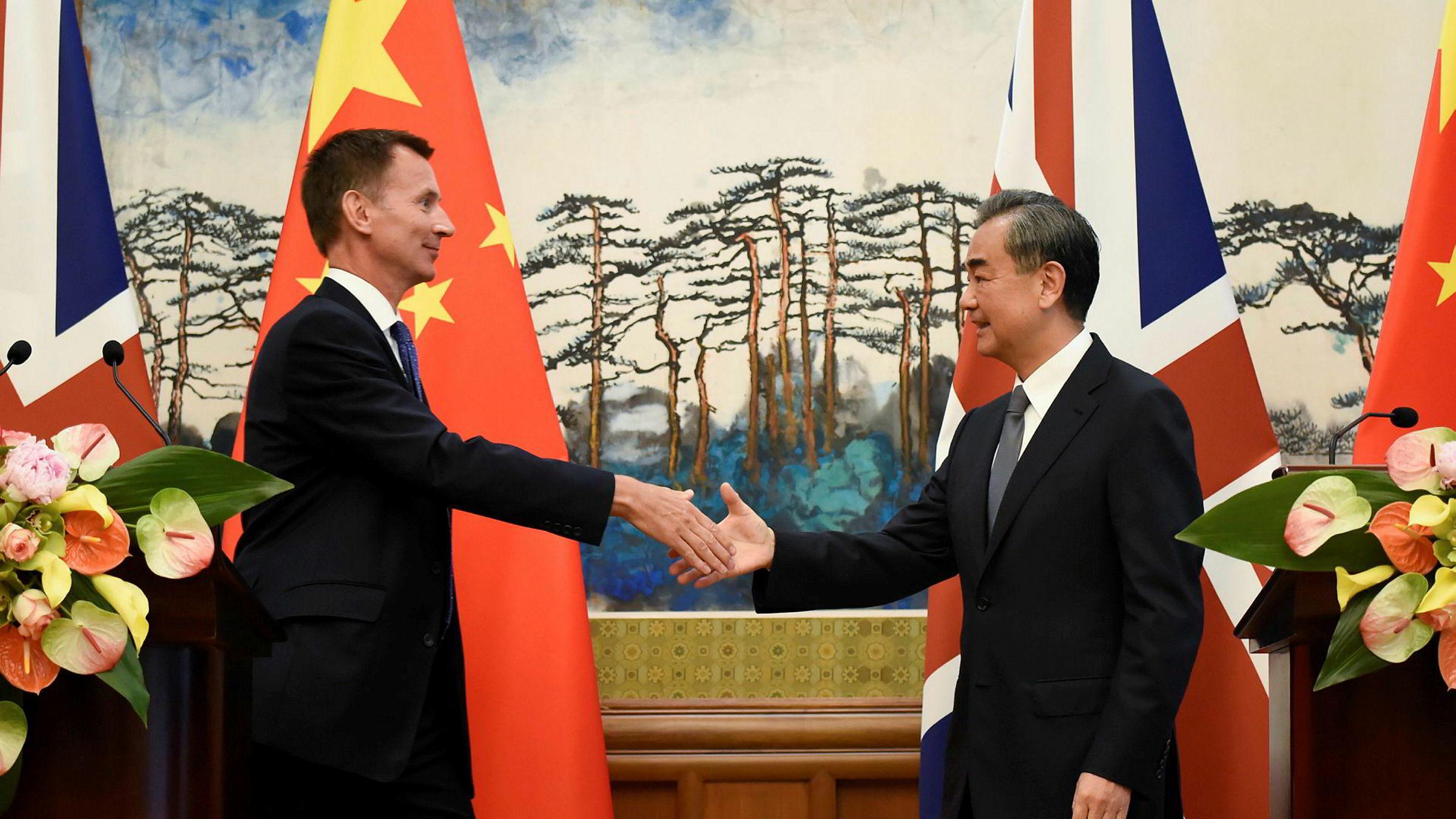 Storbritannias utenriksminister Jeremy Hunt tar Kinas utenriksminister Wang Yi i hånden etter en pressekonferanse i Beijing.