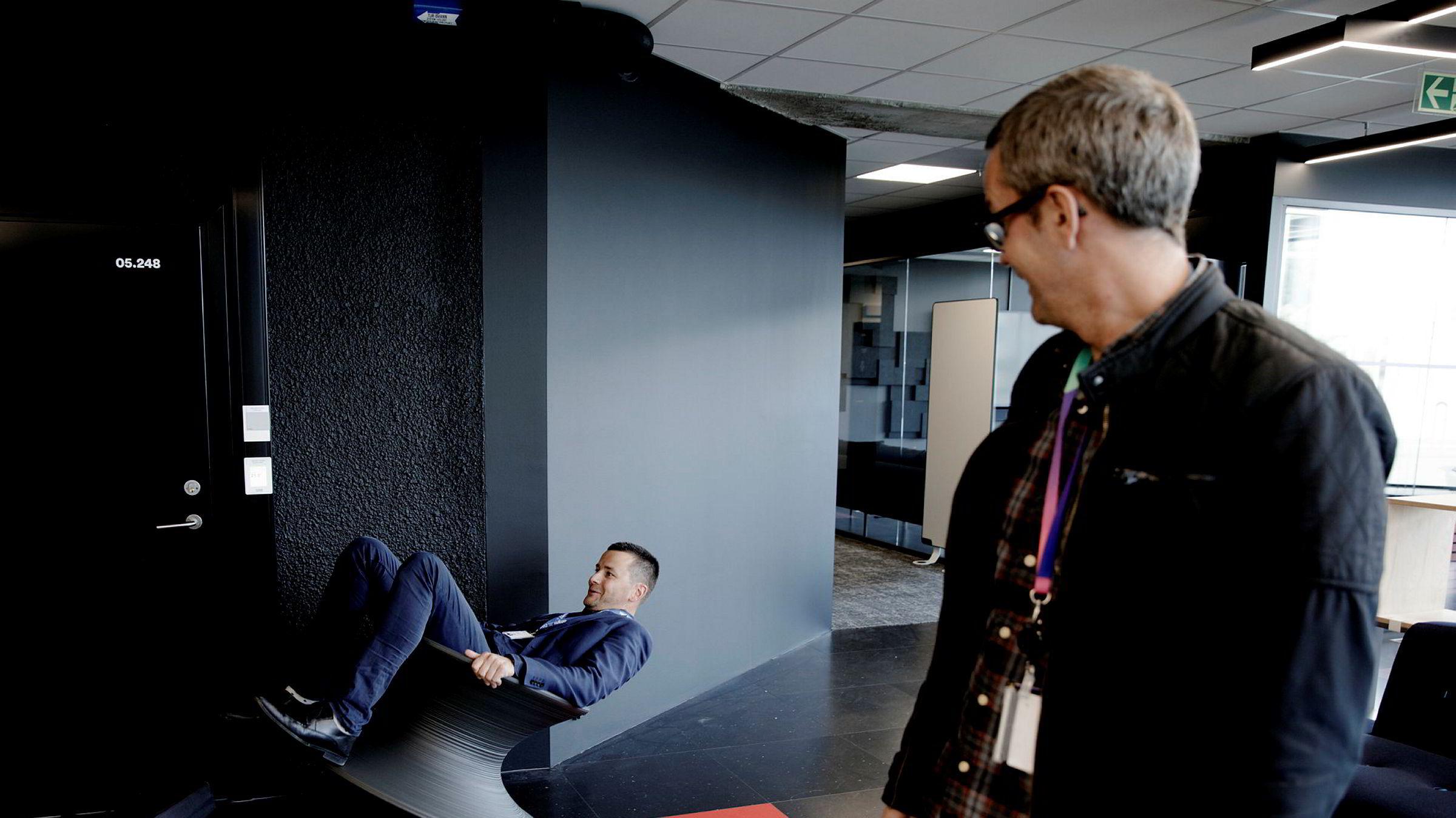 – Slike møbler har ikke vi, sier ansvarlig redaktør Øyulf Hjertenes i Bergens Tidende om innredningen av TV 2s nye kontorlokaler. Administrasjonssjef i nyhets- og sportsredaksjonen Roy Tore Jensen i TV 2 ser på.