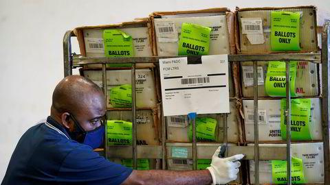 En valgfunksjonær i Miami laster poststemmesedler i en bil. Sedlene skal fraktes til velgere som har søkt om å stemme i det kommende presidentvalget via posten.
