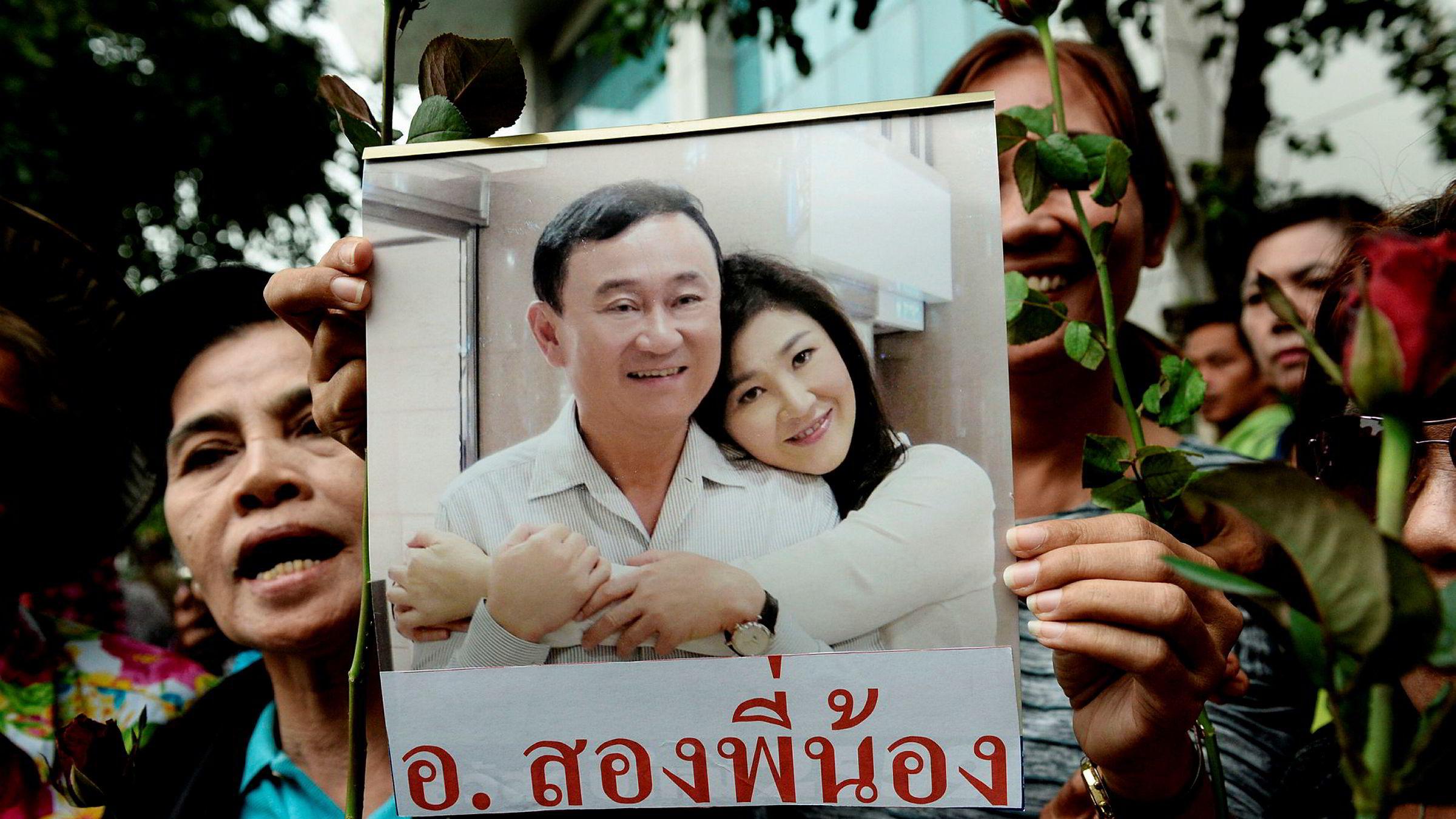 Bildet, som ble tatt i august, viser en kvinne som holder opp et bilde av Thailands tidligere statsminister Yingluck Shinawatra og broren Thaksin Shinawatra.