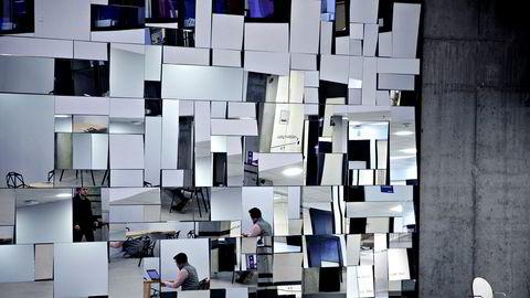 Studenter ved Norges Handelshøyskole i Bergen jobber på sine laptoper og speiles i veggkunsten.