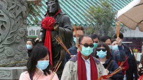 Besøkende var iført masker da de samlet seg ved Wong Tai Sin-tempelet i Hongkong lørdag for å be og feire nyttår. Foto: AP / NTB scanpix