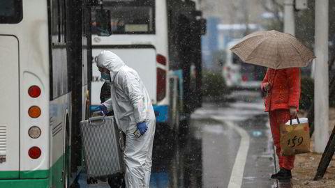 En arbeider i beskyttelsesutstyr hjelper en pasient som ankommer et sykehus i Hubei-provinsen. Foto: Chinatopix via AP / NTB scanpix