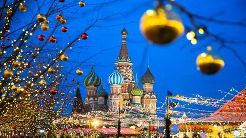People walk in Red Square decorated for Christmas and New Year celebrations, with the St. Basil's Cathedral in the background in Moscow, Russia, Saturday, Dec. 21, 2019. (AP Photo/Pavel Golovkin)