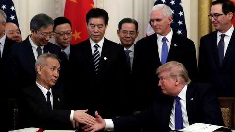 USAs president Donald Trump og Kinas visestatsminister Liu He tar hverandre i hånden etter å ha signert fase 1 av handelsavtalen mellom de to landene onsdag.