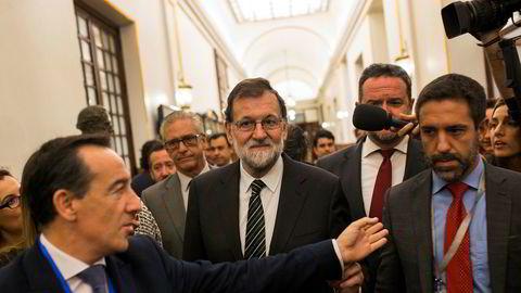 Spanias statsminister Mariano Rajoy (i midten) blir intervjuet av journalister mens han forlater den spanske parlamentet onsdag.