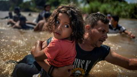 Luis Acosta hjelper femåringen Angel Jesus, begge fra Honduras, over Suchiate-elven mellom Mexico og Guatemala. Fotograf Adrees Latif vant Pulitzer-prisen for bildet i fjor, i kategorien «breaking news».