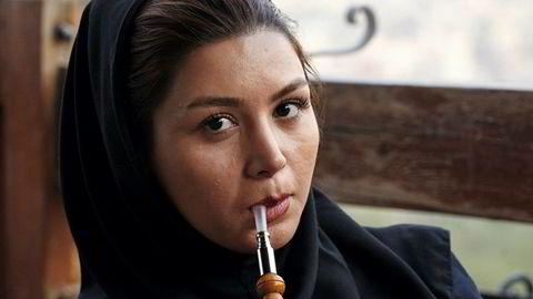 Fredspipe. Park-e-Jamshidiyeh ligger på en høyde utenfor Teheran, og er et av stedene unge tehranere – også ugifte par – går for å slippe unna trafikk, støy, skitt og voktende blikk. Kvinnen på bildet ønsket ikke navnet sitt i avisen.