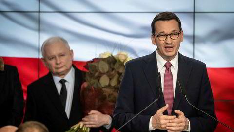 Polens statsminister Mateusz Morawiecki holder tale etter at resultatene fra valgdagsmålingen ble klare søndag 13. oktober. Partileder i Lov- og rettferdighetspartiet (PiS) Jaroslaw Kaczynski ser på i bakgrunnen.