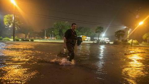 En mann vader igjennom en oversvømt strandvei idet sentrum av orkanen Nate nærmer seg Biloxi i Mississippi.