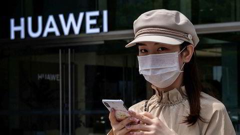 «Har jobbet mye med å ordne dette til Norge, samt at utstyret er bra og nødvendig for Oslo. Synes dette er en fin sak», skrev Huawei til Oslo kommune. Her er en kvinne med munnbind utenfor en Huawei-butikk i Beijing i mai.