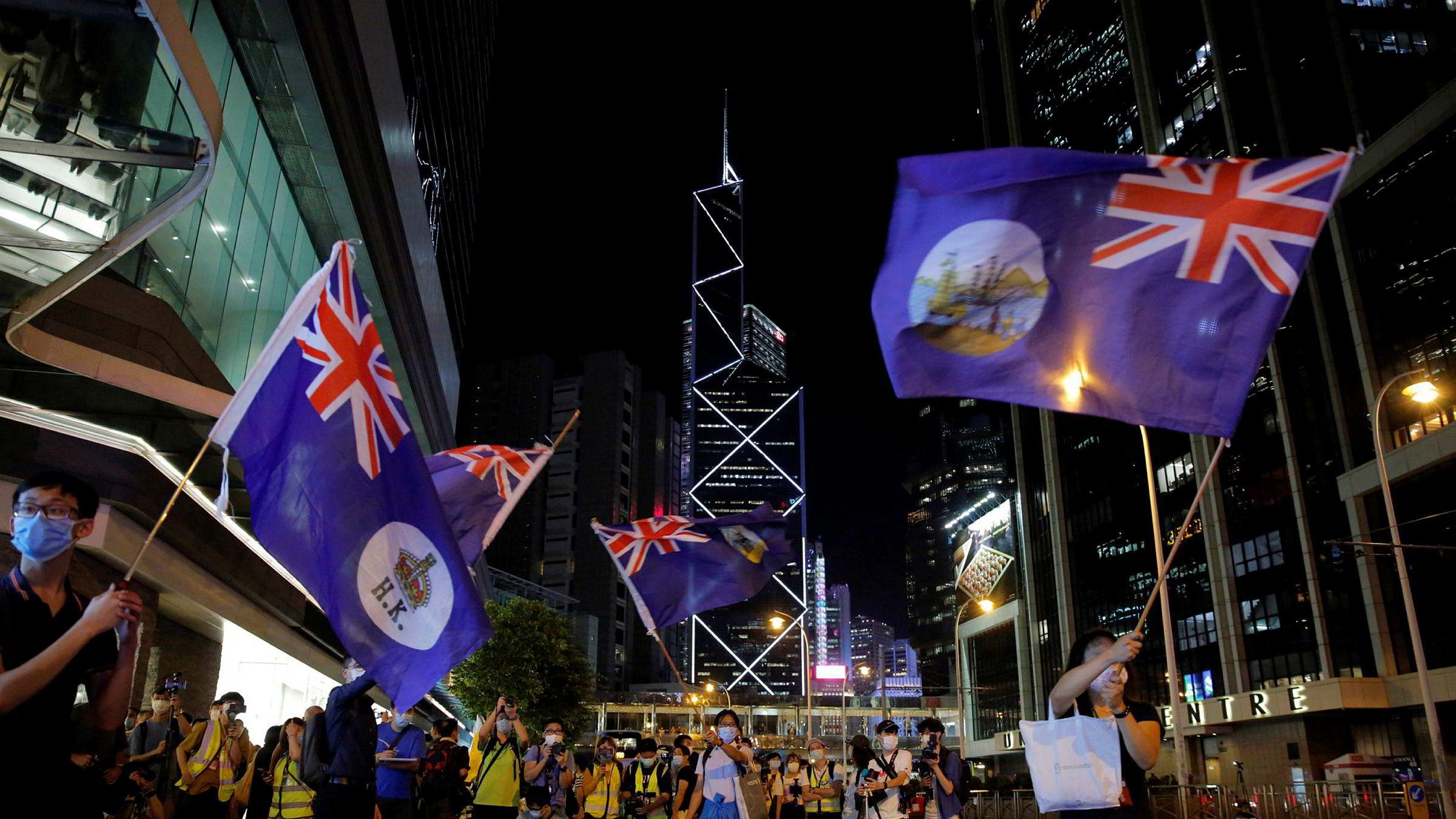 Demonstranter i Hongkong med flagg fra kolonitiden under en protest i forrige uke. Foto: Kin Cheung / AP / NTB scanpix