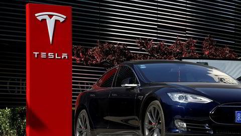 Rapport spår at Tesla vil miste lederposisjonen blant verdens produsenter av elbiler. FILE PHOTO: A Tesla car charges at a charging station in Beijing, China, April 18, 2017. REUTERS/Thomas Peter/File Photo
