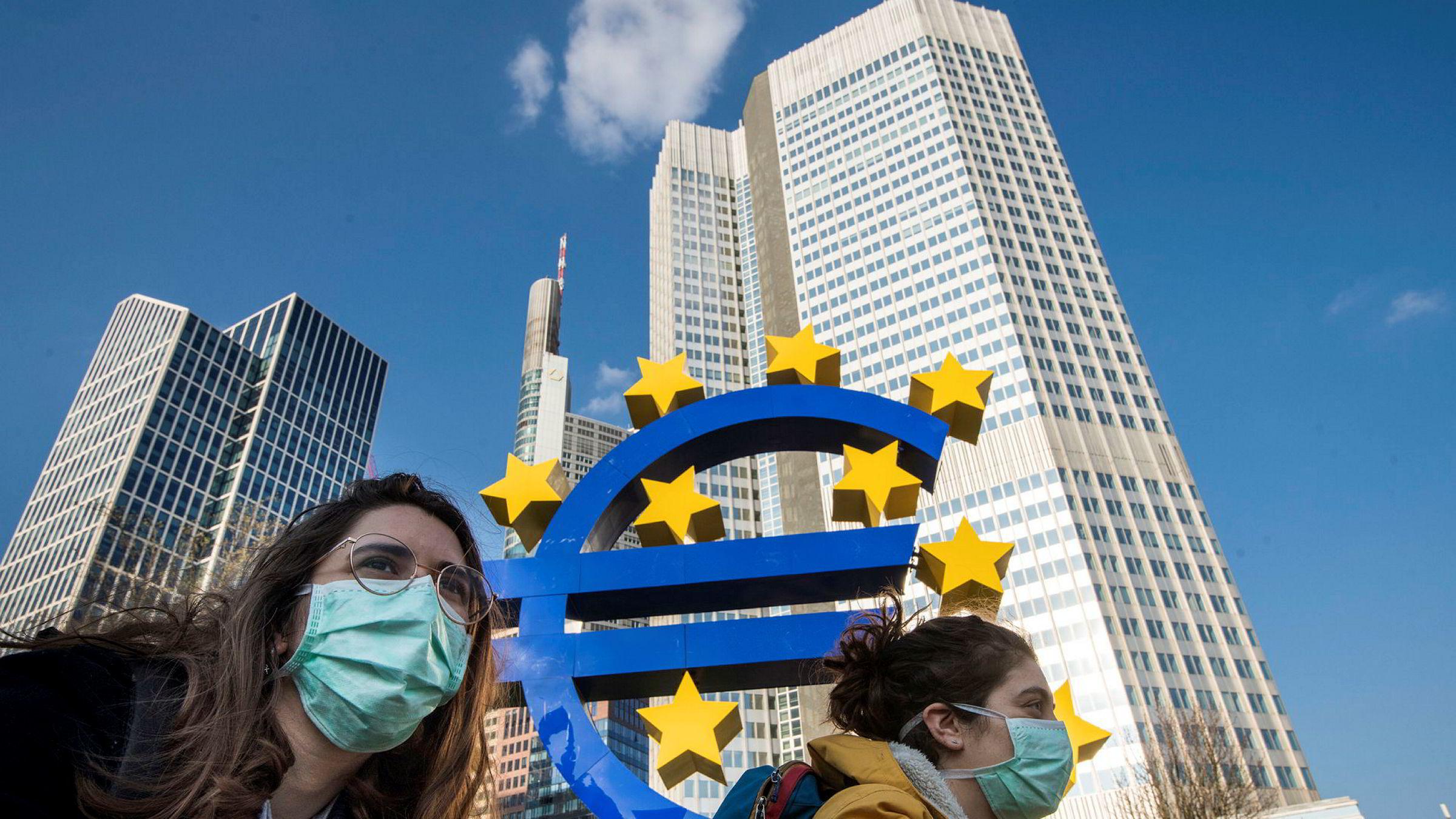 I bunnen handler det om selve eurokonstruksjonen, som aldri har vært laget for å tåle økonomisk stormvær. Her sykler to studenter med ansiktsmasker forbi en euroskulptur i Frankfurt i Tyskland.