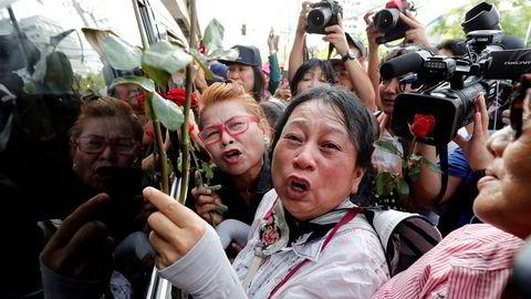 Tilhengere av den tidligere thailandske statsministeren Yingluck Shinawatra protesterer utenfor rettslokalet fredag, der hun skulle ha dukket opp. Hun kom aldri.