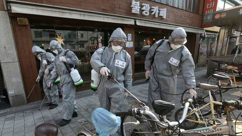 Sørkoreanske soldater sprayer desinfeksjonsmiddel mot det nye koronaviruset på en gate i Seoul i Sør-Korea fredag formiddag. Over 6200 mennesker er smittet i Sør-Korea.